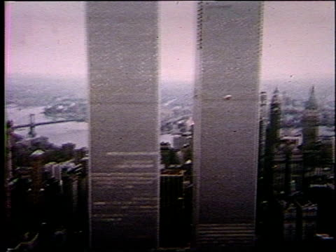 Helicopter POV passing WTC Towers, Brooklyn Bridge & New York Harbor in BG. Narrator talks about white-collar crime.