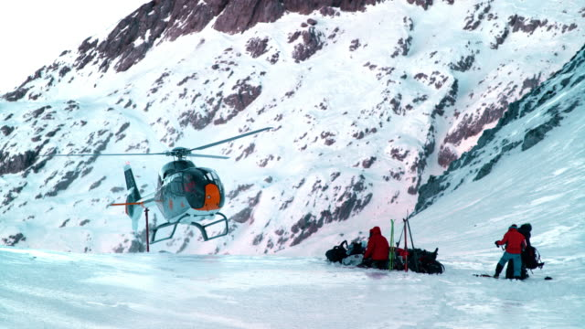 slo mo helicopter picking up the expedition team on icy mountain - ice stock videos & royalty-free footage