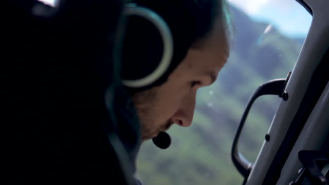 Helicopter pilot looks out window while flying