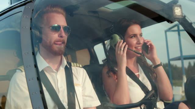 vídeos de stock, filmes e b-roll de piloto de helicóptero, sentado no cockpit com passageira - cabine de piloto de avião