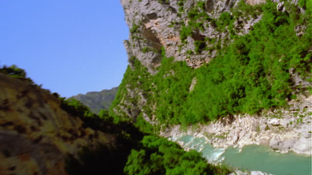 AERIAL helicopter point of view following river through mountain gorge / Gorges du Verdon / Provence, France