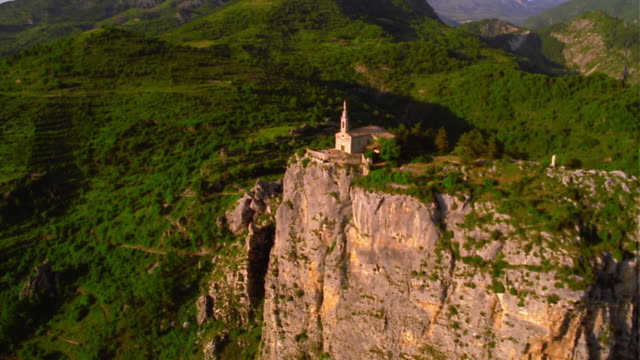 aerial helicopter point of view wide shot past church on cliff surrounded by mountains /castellane / provence, france - frankreich stock-videos und b-roll-filmmaterial