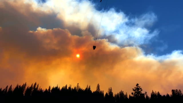 A helicopter prepares to drop water on the Camp Fire as it burns in the hills on November 11 2018 near Cresta California