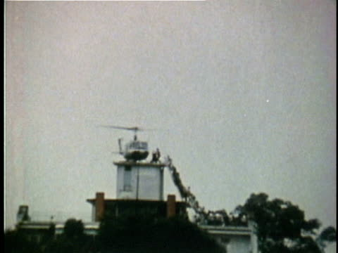helicopter preparing to take off with south vietnamese refugees from rooftop helipad after the fall of saigon / saigon south vietnam - 1975年点の映像素材/bロール