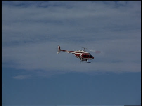 a helicopter releases water from the air. - retter rettungsaktion stock-videos und b-roll-filmmaterial