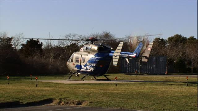 vídeos de stock e filmes b-roll de a helicopter rises from a helipad. - descolar atividade