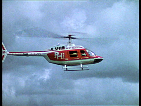 Helicopter rotor blades slowed down to crawl as it hovers in cloudy sky