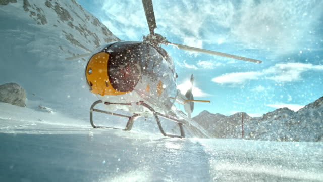 slo mo helicopter rotors make ice particles shine in sun - helicopter stock videos & royalty-free footage
