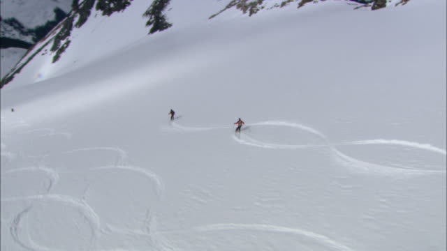 helicopter shadow finds skiers zigzagging down a snowy mountain. - downhill skiing stock videos & royalty-free footage