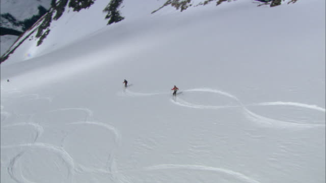 helicopter shadow finds skiers zigzagging down a snowy mountain. - winter sport stock videos & royalty-free footage
