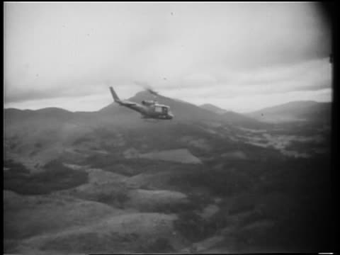 helicopter shooting rockets flying over mountains in vietnam war - 1966 bildbanksvideor och videomaterial från bakom kulisserna