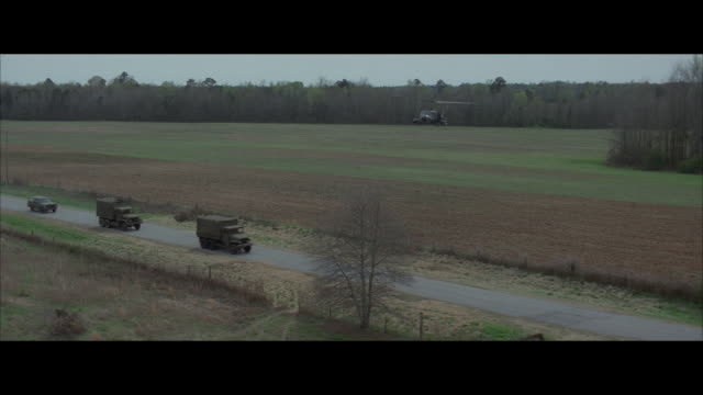 aerial, helicopter shooting to military convoy on country road - convoy stock videos and b-roll footage