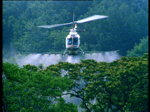 helicopter sprays insecticide onto forest - insecticide stock videos & royalty-free footage