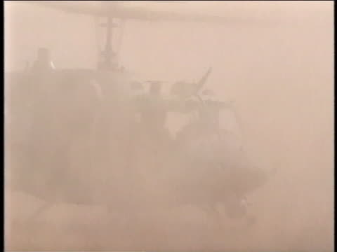 helicopter stirs up a cloud of dust as it lands. - al fallujah stock videos & royalty-free footage