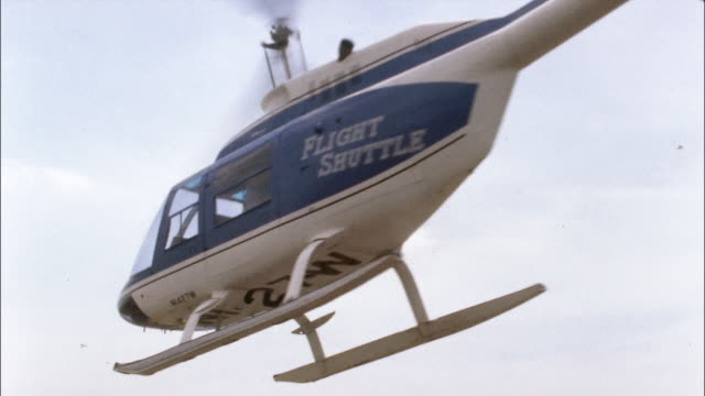 A helicopter takes off from a helipad and flies away.