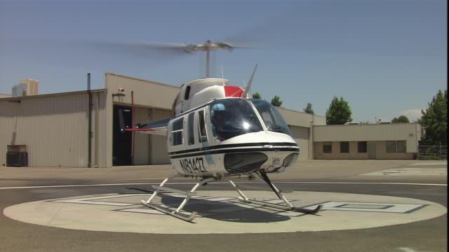 vídeos de stock e filmes b-roll de a helicopter takes off from a helipad. - descolar atividade