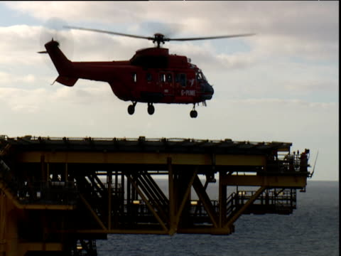 vídeos de stock, filmes e b-roll de helicopter takes off from oil platform - helicopter landing pads