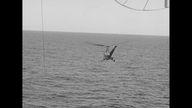 vídeos de stock, filmes e b-roll de helicopter taking off from deck of carrier uss saidor / man on deck filming with camera / helicopter taking off flying away from carrier / man on... - oceano pacífico do sul
