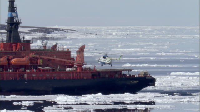 ws, ts, helicopter taking off from icebreaker traveling through ice covered ocean, russia - russia stock videos and b-roll footage