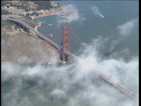 helicopter view flying over golden gate bridge with traffic moving along through wispy clouds. calm sea and bay below - 1994 stock videos and b-roll footage