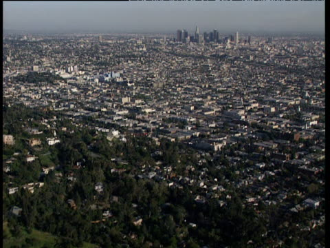 helicopter view over rows of houses and other built up areas surrounded by trees. downtown los angeles skyline just visible in distance - doppelhaus stock-videos und b-roll-filmmaterial
