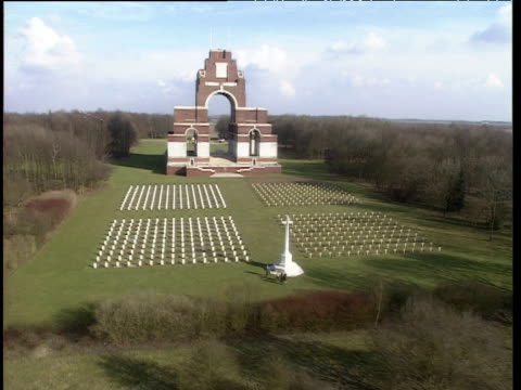Helicopter view over white gravestones on well kept grass in front of Thiepval memorial Somme