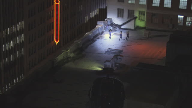 AERIAL Helicopter with navigation lights using searchlight to illuminate suspects and police officers on flat rooftop of building across street from Orpheum Theatre's neon sign, then flying away over rooftops / Los Angeles, California, United States