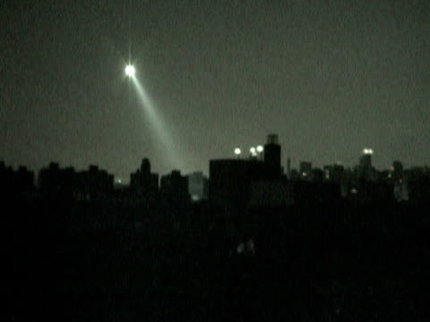 helicopter with searchlight flying above rooftops during citywide blackout on august 14 2003 / queens new york usa / audio - 2003年点の映像素材/bロール