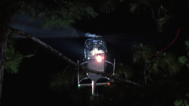 MS Helicopter with searchlight flying low over two story suburban house and tree tops