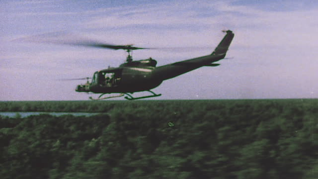 Helicopters and airplanes flying over jungle and explosion in the distance / Vietnam