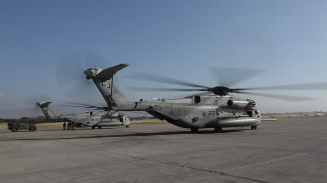 U.S. CH-53E helicopters are positioned on a runway as former U.S. President Bill-Clinton visits Haiti.