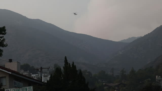 helicopters flying overhead to drop water to extinguish bobcat fire in angeles national forest. the u.s. west is bracing for another blast of dry and... - helicopter landing stock videos & royalty-free footage