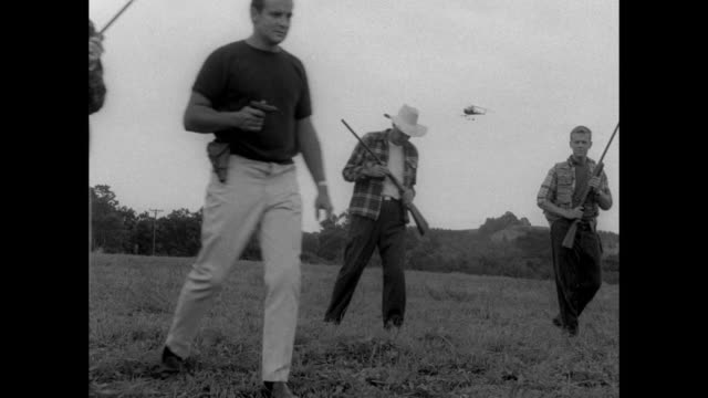 1968 Helicopters, militia men with guns and police with dogs gather in early morning