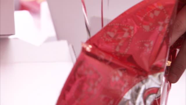 vídeos y material grabado en eventos de stock de helium expands a shiny, red balloon. - globo de helio