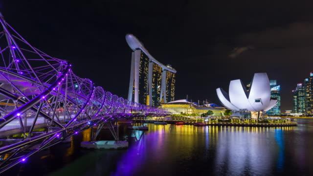 tl ws helix bridge across marina bay and singapore skyline at night - helix bridge stock videos & royalty-free footage
