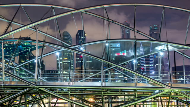 Helix pedestrian bridge in Marina Bay in Singapore. It is a part of the walkway around Marina Bay. Blurred people walking inside