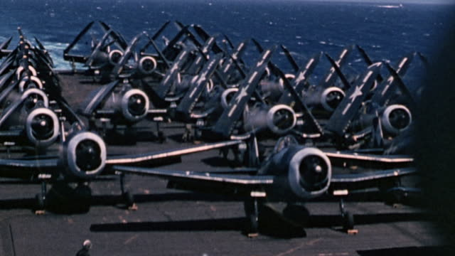 Hellcats warming up engines on flight deck of USS Essex and F4U Corsairs unfolding wings and taking off