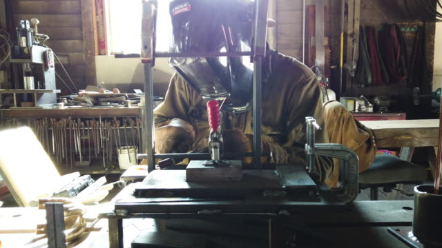 hellgate forge fabricator and welder troy bloom welds handmade fixtures at the company's shop inside the former lumber mill's 100-year-old machine... - schweißen stock-videos und b-roll-filmmaterial