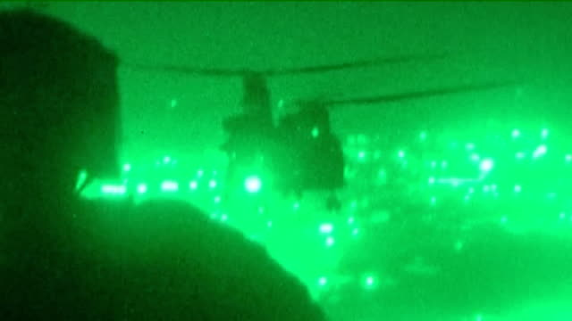 helmand ext / night green night vision shot back view of british soldier sitting at open cockpit of helicopter as flying over countryside looking out... - night vision stock-videos und b-roll-filmmaterial