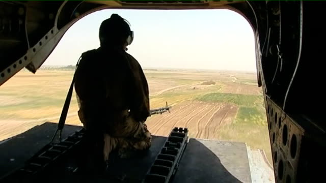 douglas alexander mp sitting in helicopter as flying into helmand british soldier seated at open hatch of helicopter as flying over open countryside... - ダグラス アレキサンダー点の映像素材/bロール