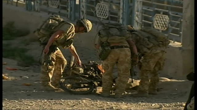 british troops in sangin locals and soldiers clear debris from street after suicide bomb wrecked motorcycle in aftermath of suicide bomb local police... - bomb stock videos & royalty-free footage