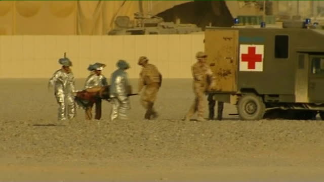 helmand province: camp bastion: ext chinook helicopter landing at camp bastion - injured british soldiers on stretchers carried from helicopter to... - british military stock videos & royalty-free footage