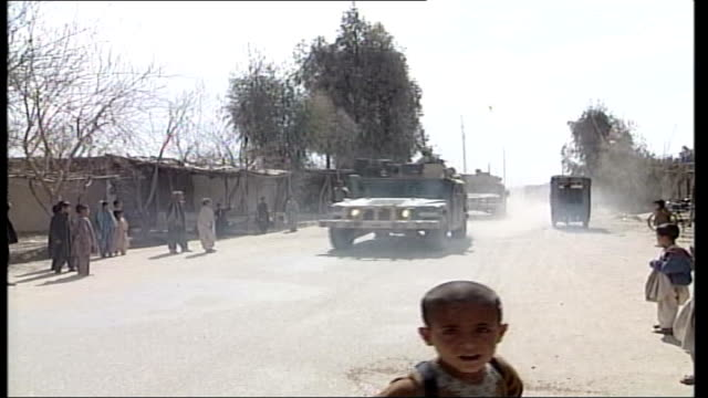 helmand province lashkar gar ext british soldier on patrol along street followed by group of children british soldier stands with local children who... - military invasion stock videos and b-roll footage