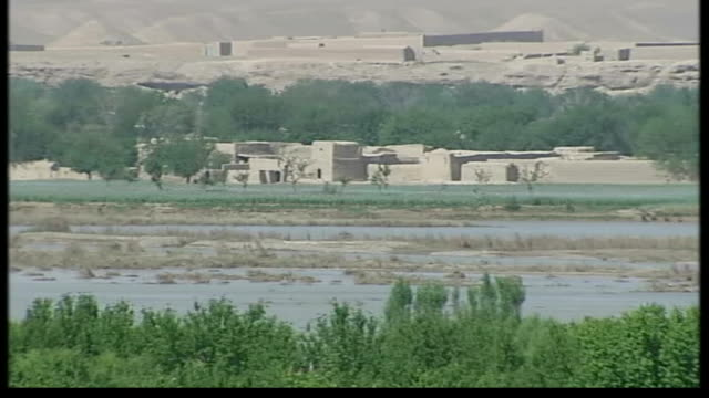 problems facing Afghan security forces Agricultural fields with hills in distance Village buildings locals and camels in fields with mountains in...