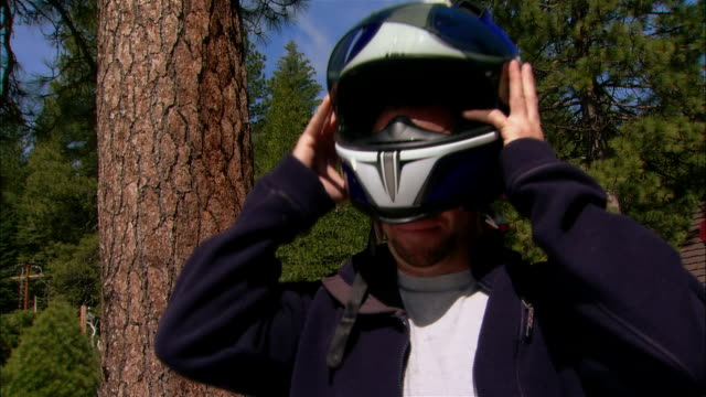cu helmet on back of motorcycle/ tu ms portrait motorcyclist standing in forest + removing helmet/ fresno county, california - taking off点の映像素材/bロール