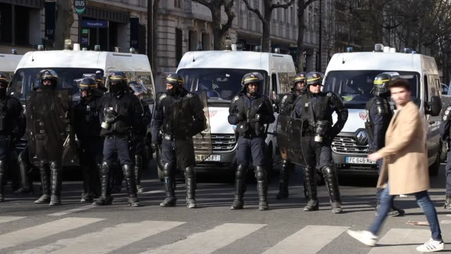 helmeted policemen block the street with trucks with yellow vests avenue kléber 75016 paris - 機動隊点の映像素材/bロール