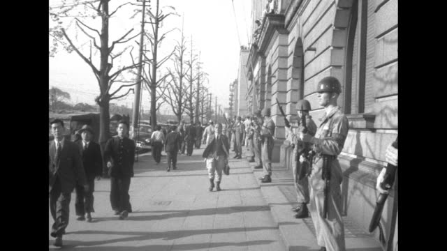 vídeos de stock e filmes b-roll de helmeted, uniformed japanese policemen stand with batons at the ready / a long line of protesters trots along and avenue with the japanese diet... - maça