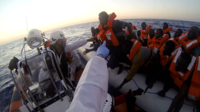 helmetmounted camera footage shows refugees and migrants in a small rubber boat being rescued by crew members from the migrant offshore aid station... - mittelmeer stock-videos und b-roll-filmmaterial