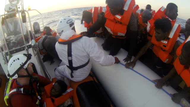 helmet-mounted camera footage shows refugees and migrants in a small rubber boat being rescued by crew members from the migrant offshore aid station... - rescue stock videos & royalty-free footage