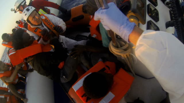 stockvideo's en b-roll-footage met helmetmounted camera footage shows refugees and migrants in a small rubber boat being rescued by crew members from the migrant offshore aid station... - vluchteling ontheemden